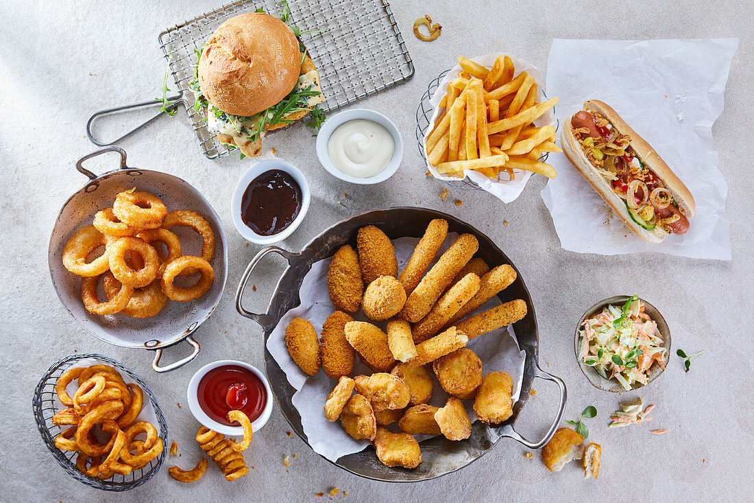 Various fast food snacks with dips, chips and coleslaw
