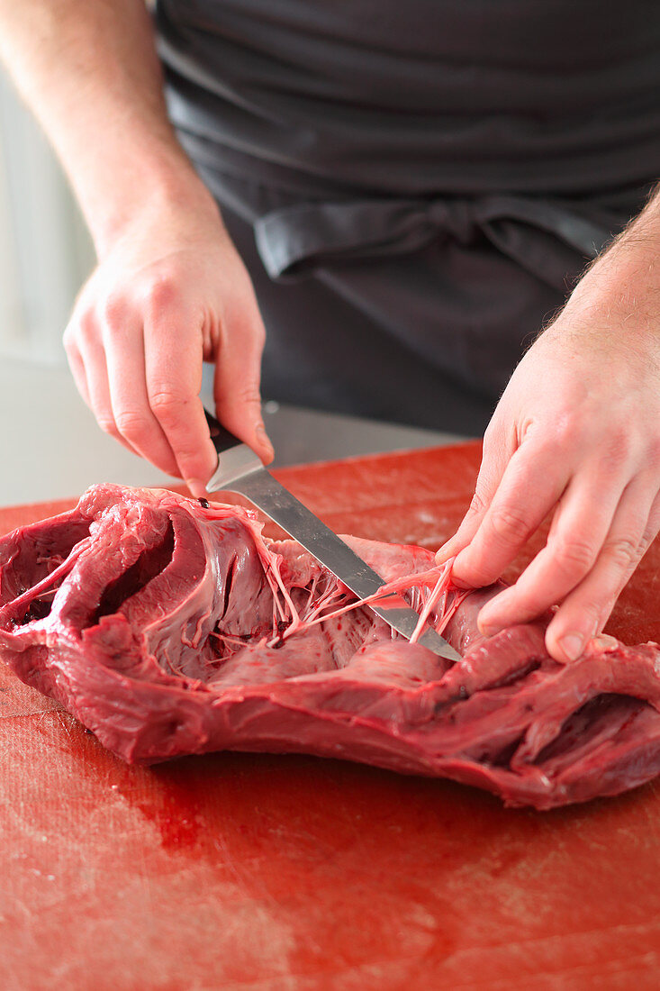 Beef heart being prepared (arteries and tendons being removed)