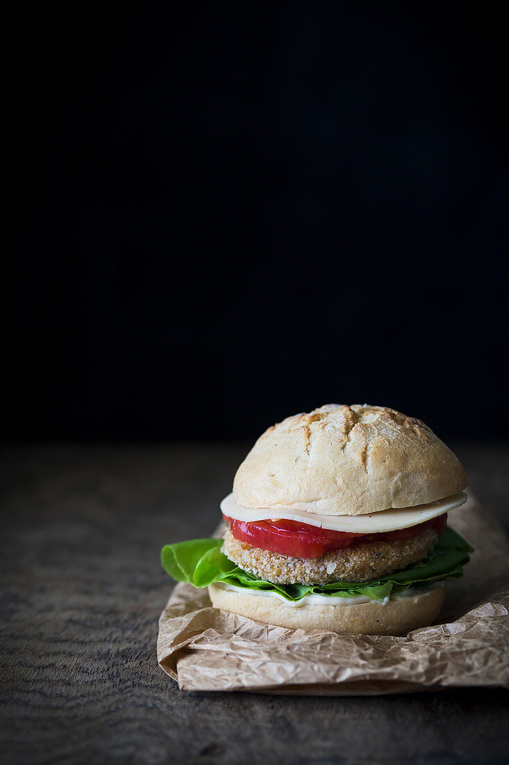 A sandwich with a chickpea patty, lettuce, tomatoes and cheese