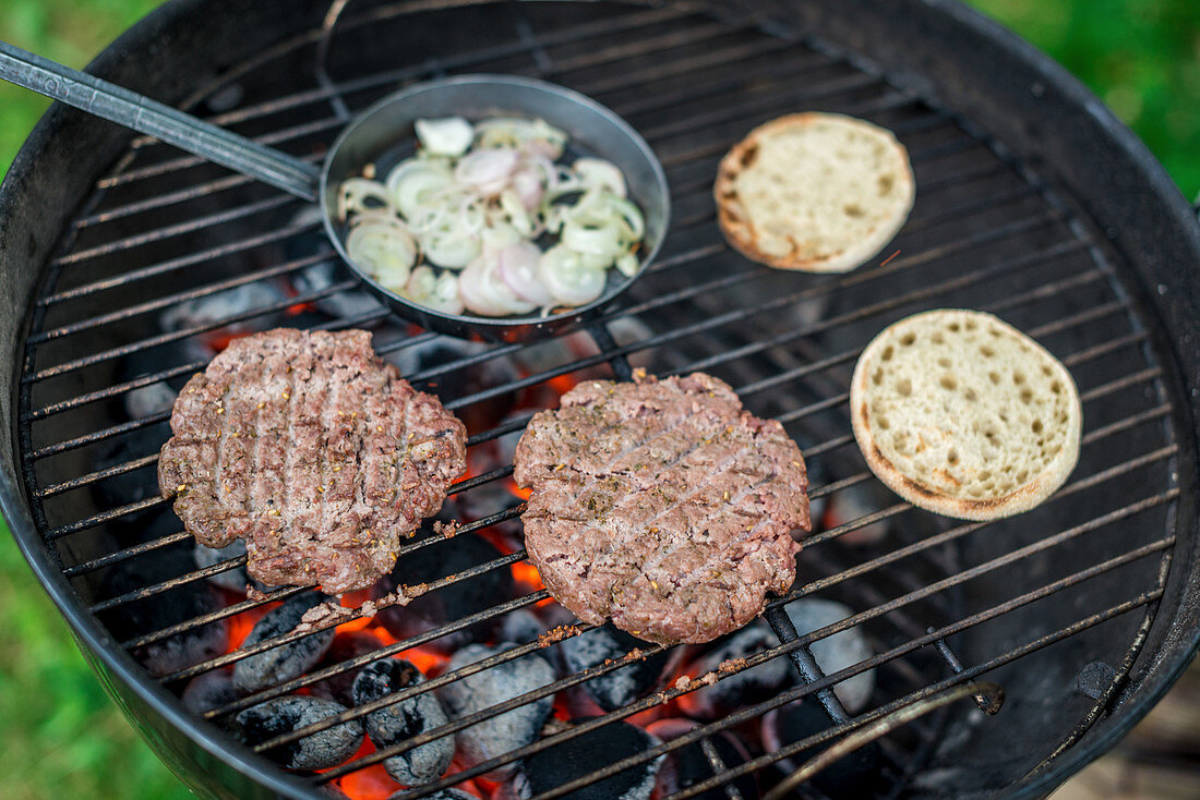 Burgers, burger buns and a pan of onion rings on a barbecue