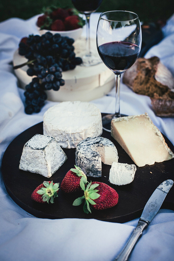 A cheese platter with strawberries and red wine on a picnic blanket