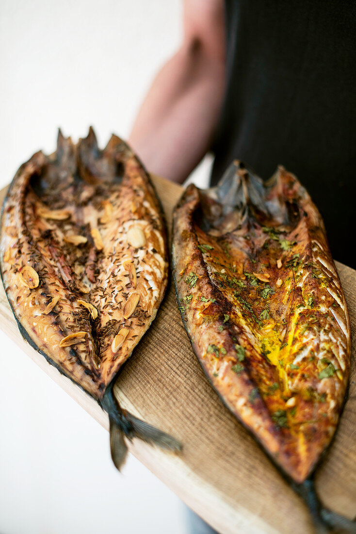 Two smoked mackerel on a wooden board
