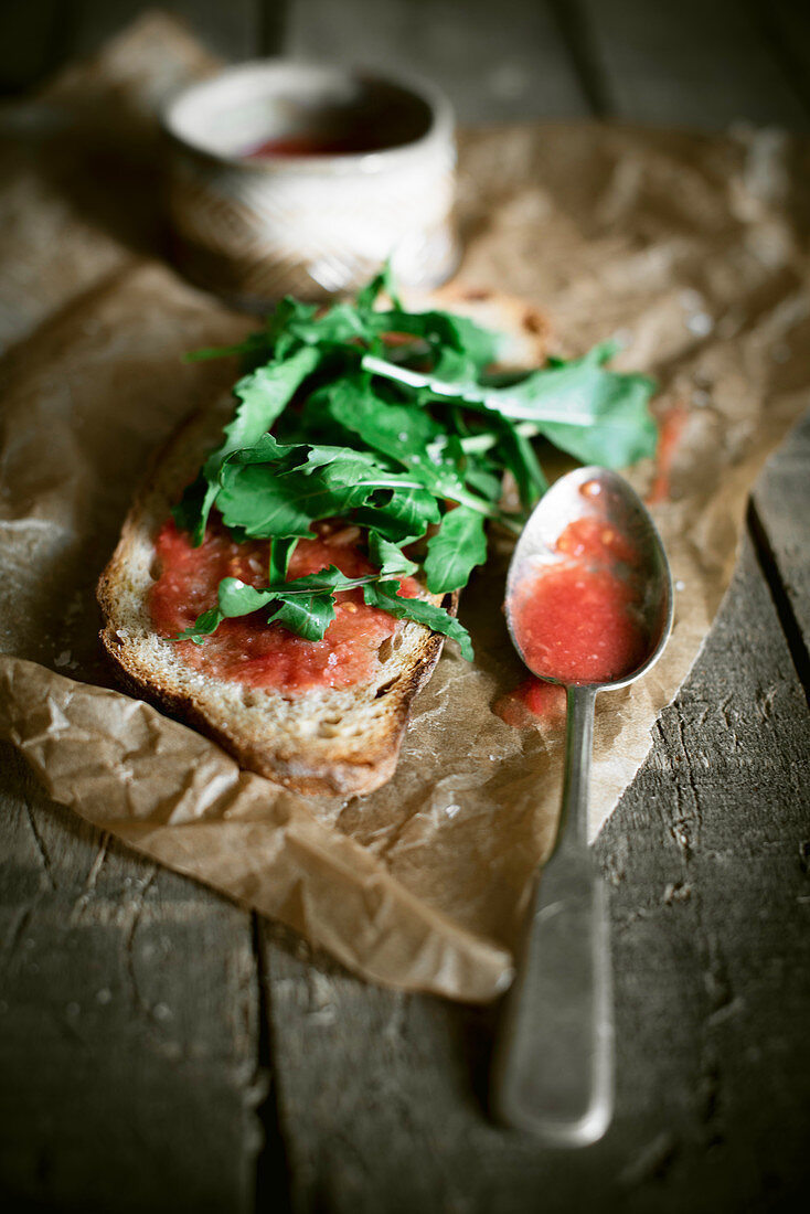 Slices of sourdough bread with raw tomato sauce and rocket
