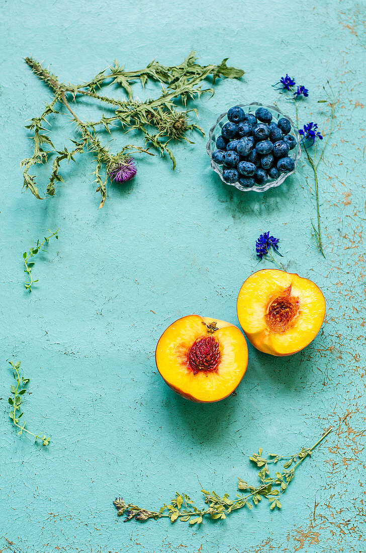 Old blue background with herbarium, blueberries and a ripe peach