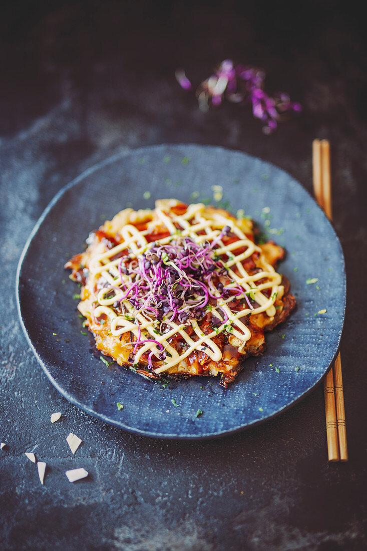 Okonomiyaki (pancake with cabbage, red ginger and bonito flakes, Japan)