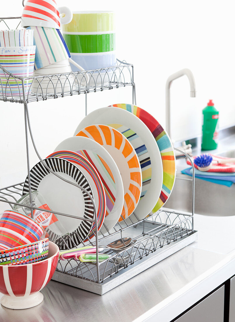 Brightly striped plates on drying rack