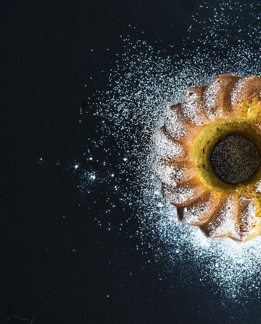 Moist orange bundt yoghurt cake with sugar powder, dark grunge background