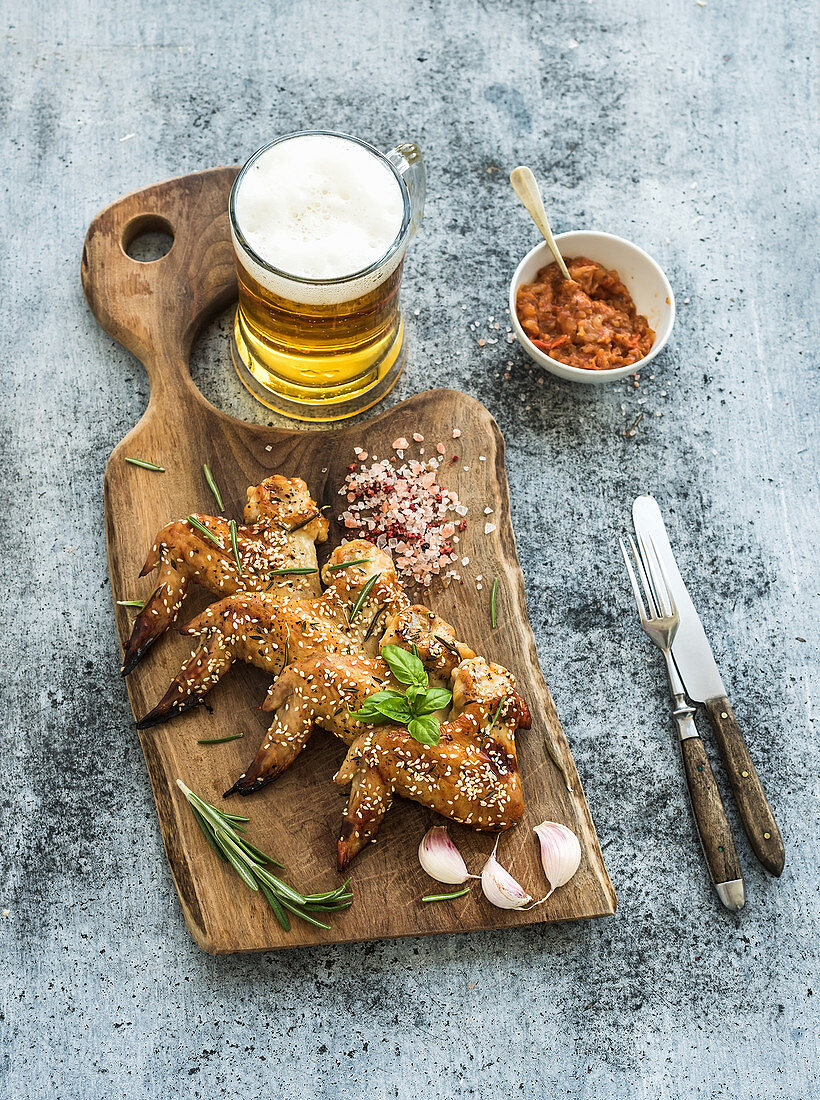 Fried chicken wings on rustic serving board, spicy tomato sauce, herbs and mug of light beer over black wooden backdrop