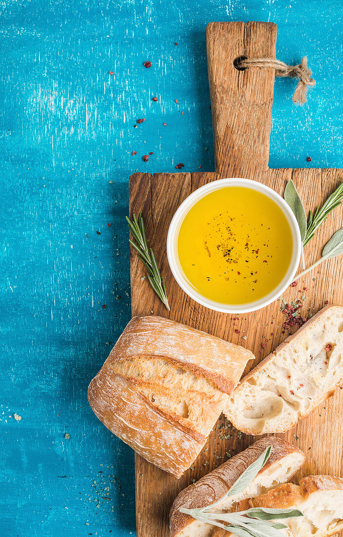 Mediterranean snacks set - Olive oil, herbs and sliced ciabatta bread