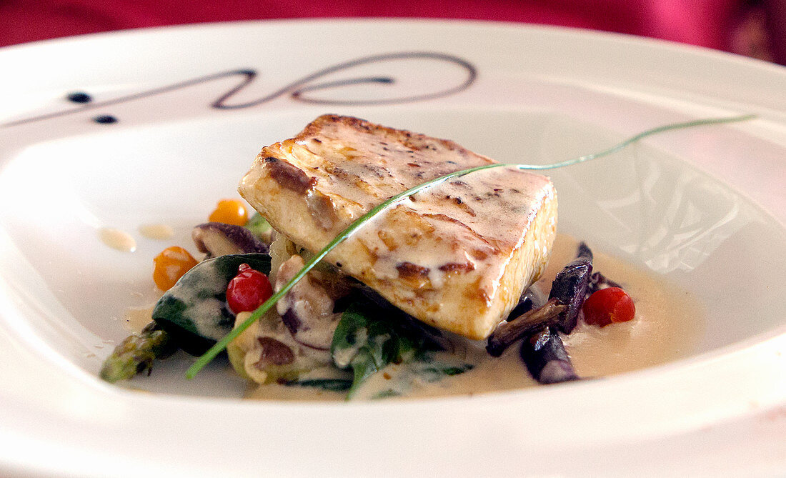 Bream fillet on a bed of vegetables with beurre blanc