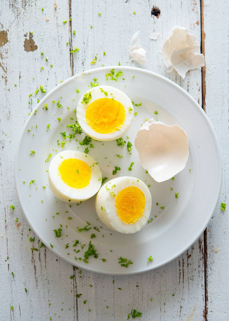 Boiled eggs, halved with parsley sprinkled on a plate (seen from above)