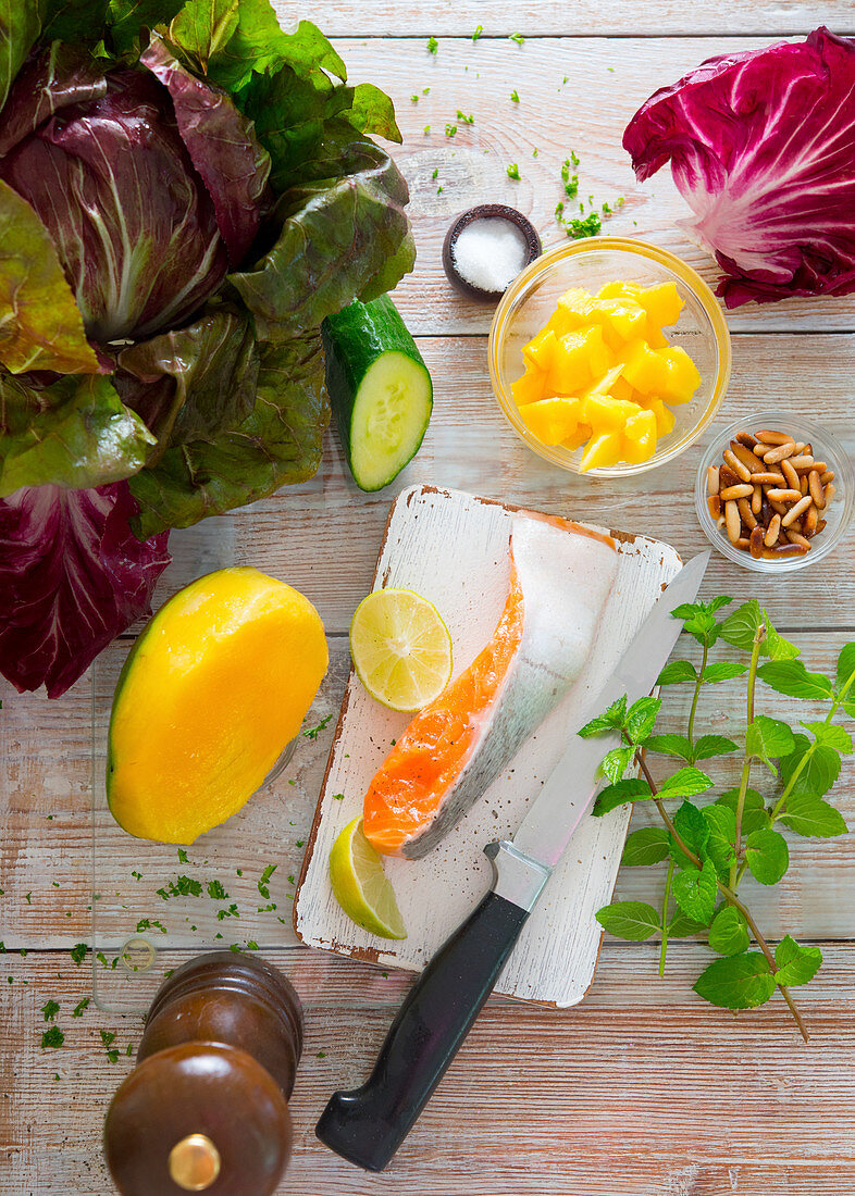 Ingredients for a salmon dish with a mango and cucumber salad and radicchio