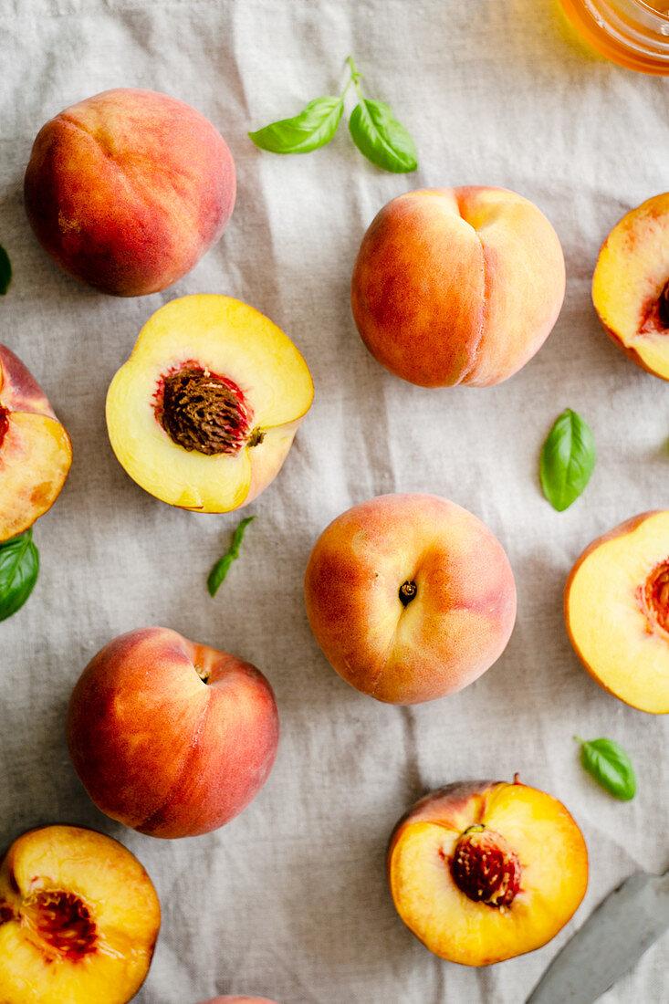 Fresh peaches and peach halves in a linen tablecloth