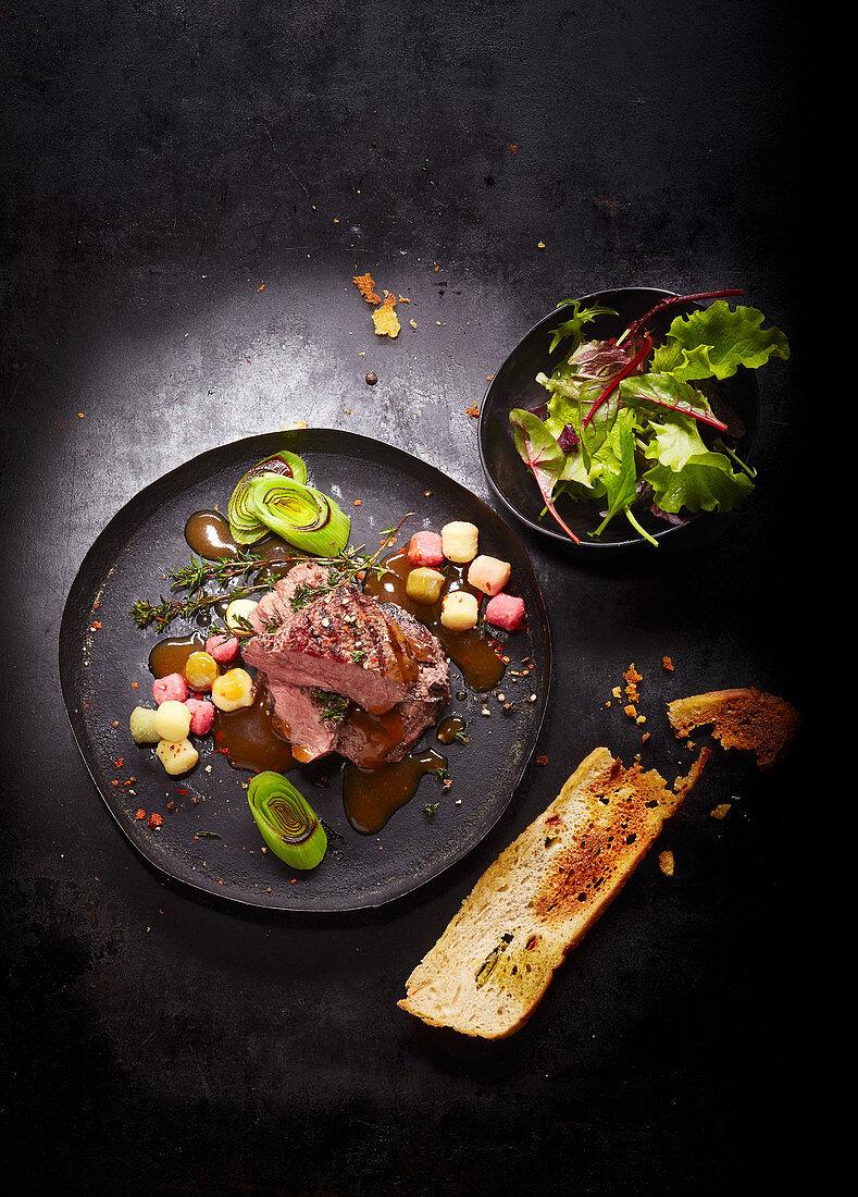 A steak dish with a garlic baguette