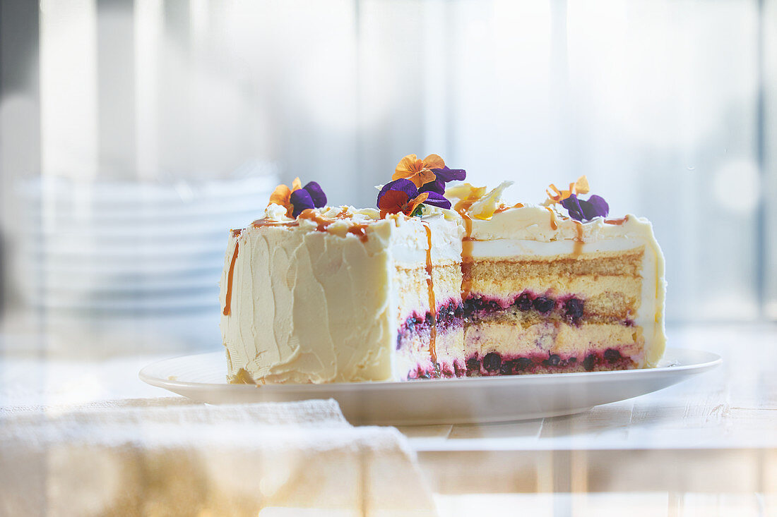 Cream cheese cake with berries and edible flowers