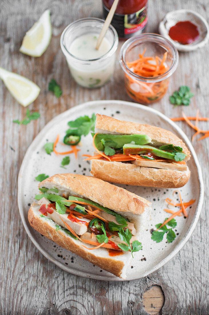 Vegan Banh mi sandwich with tofu, avocado, carrot pickles, vegan mayo and sriracha