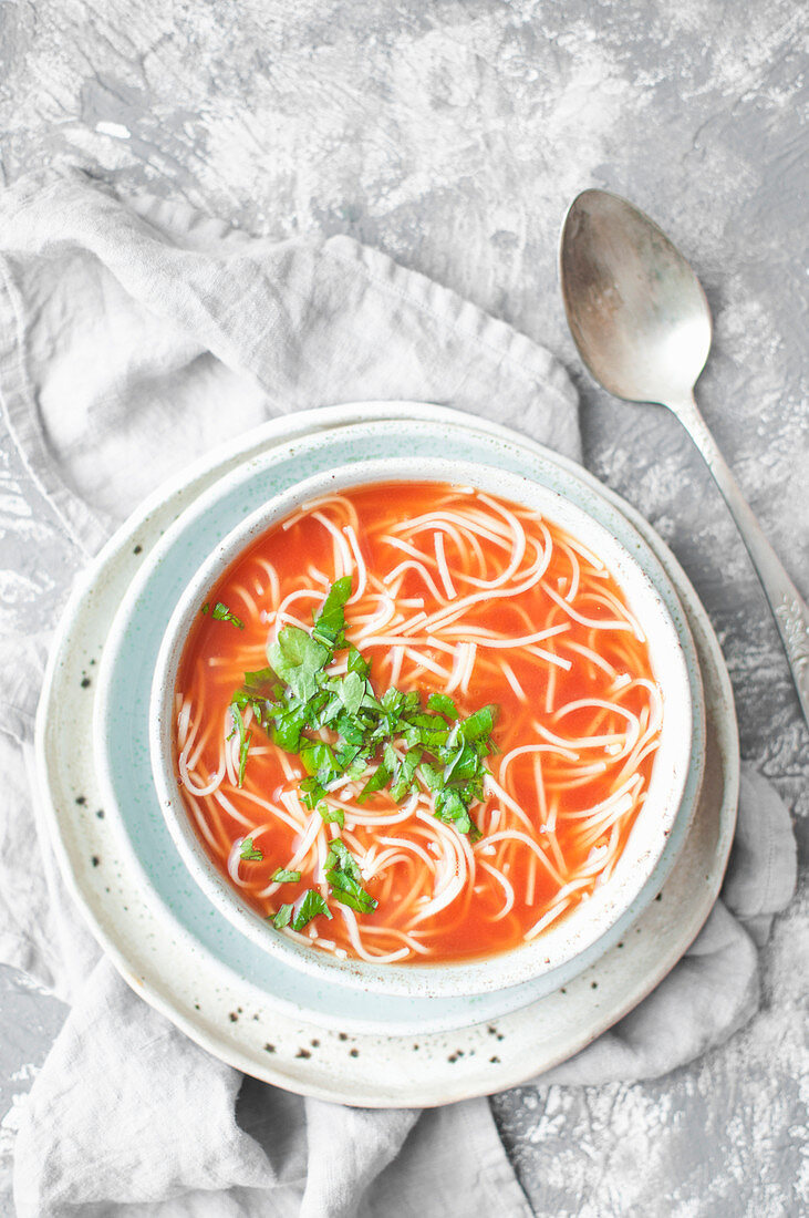 Tomato soup with noodles and chopped parsley