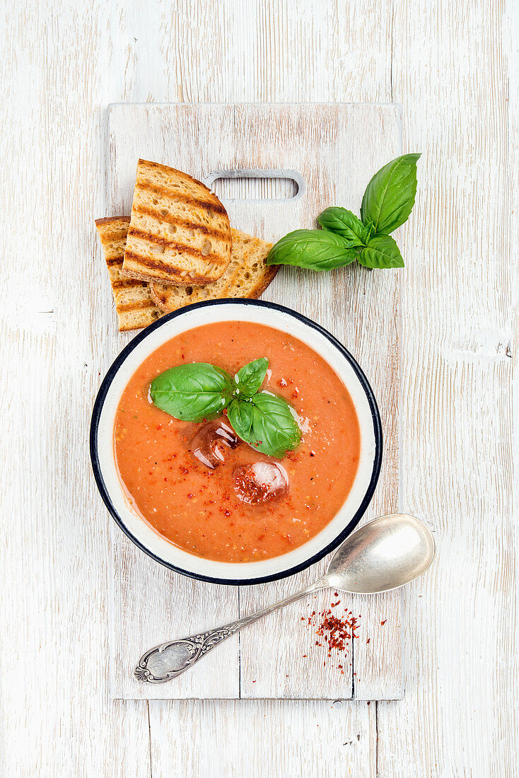 Cold tomato gazpacho soup in bowl with ice, hot pepper, basil and bread slices
