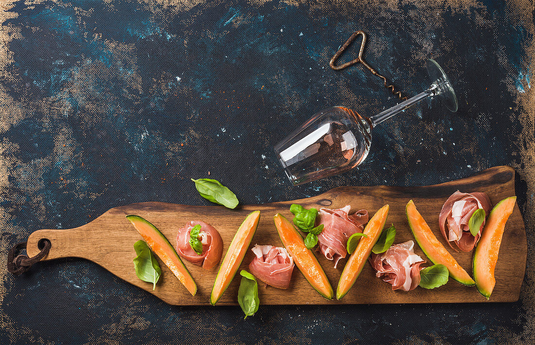 Prosciutto ham with cantaloupe melon, basil leaves and wine glass