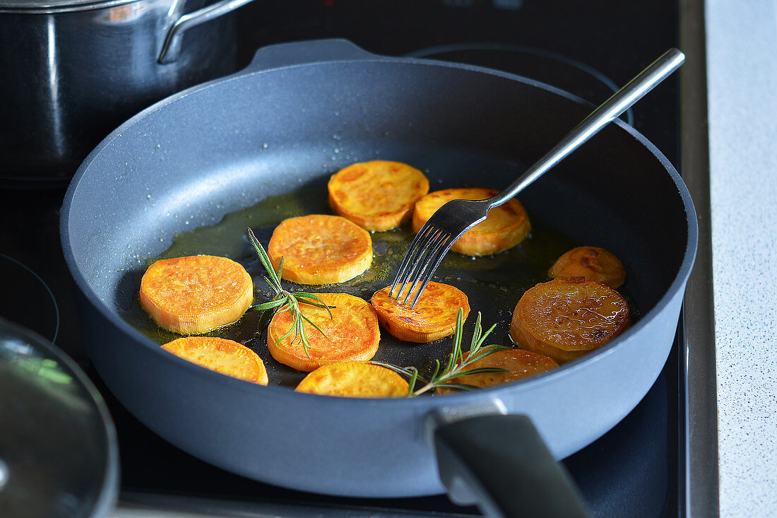 Fried sweet potato slices with oil in a pan