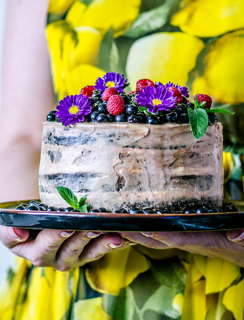 A woman in a yellow dress is holding a cake with bird cherries and flowers
