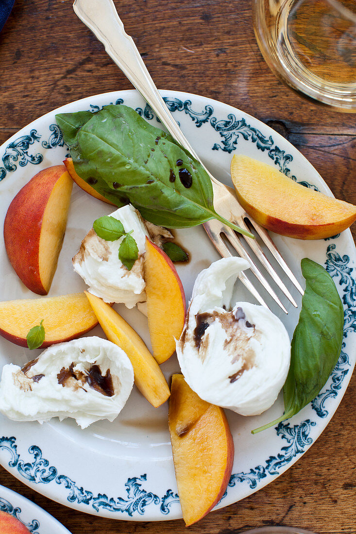 A peach, basil and buffalo mozzarella salad with balsamic and a glass of white wine