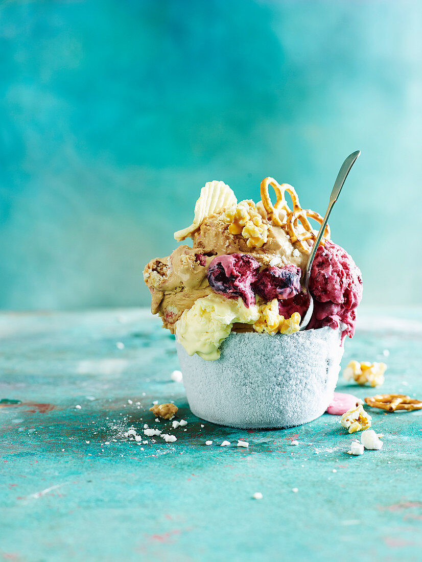 Ice cream with pretzels, crisps and popcon in a bowl