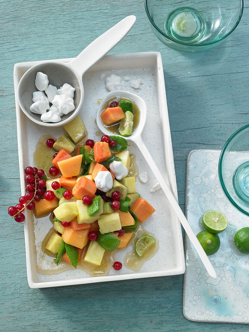 Fruit salad with melon, avocado, pineapple, papaya, redcurrant and ginger meringue dots
