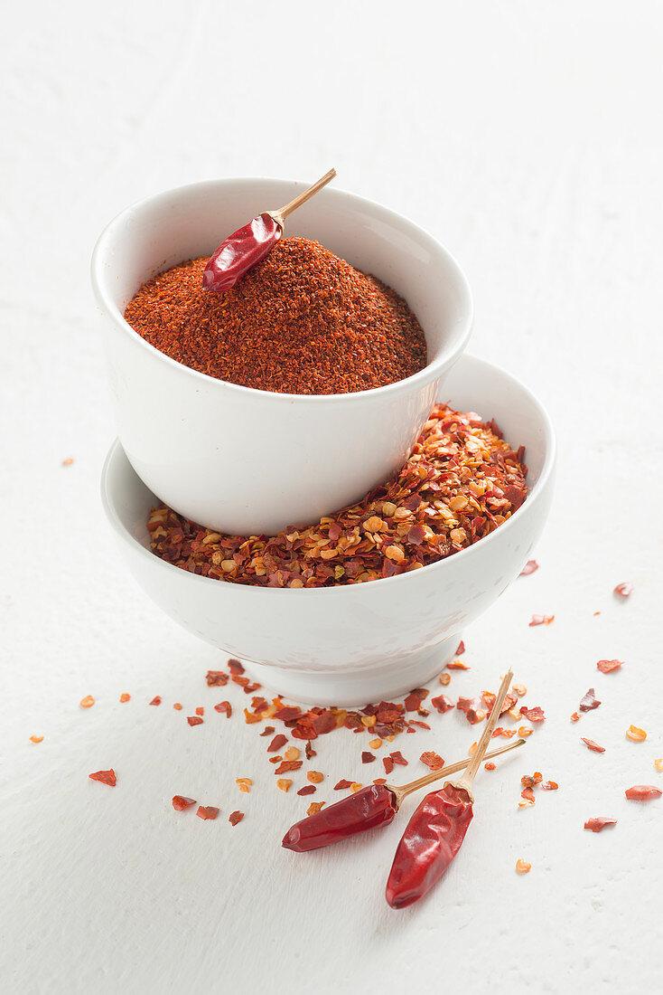 Chilli powder and chilli flakes in white bowls