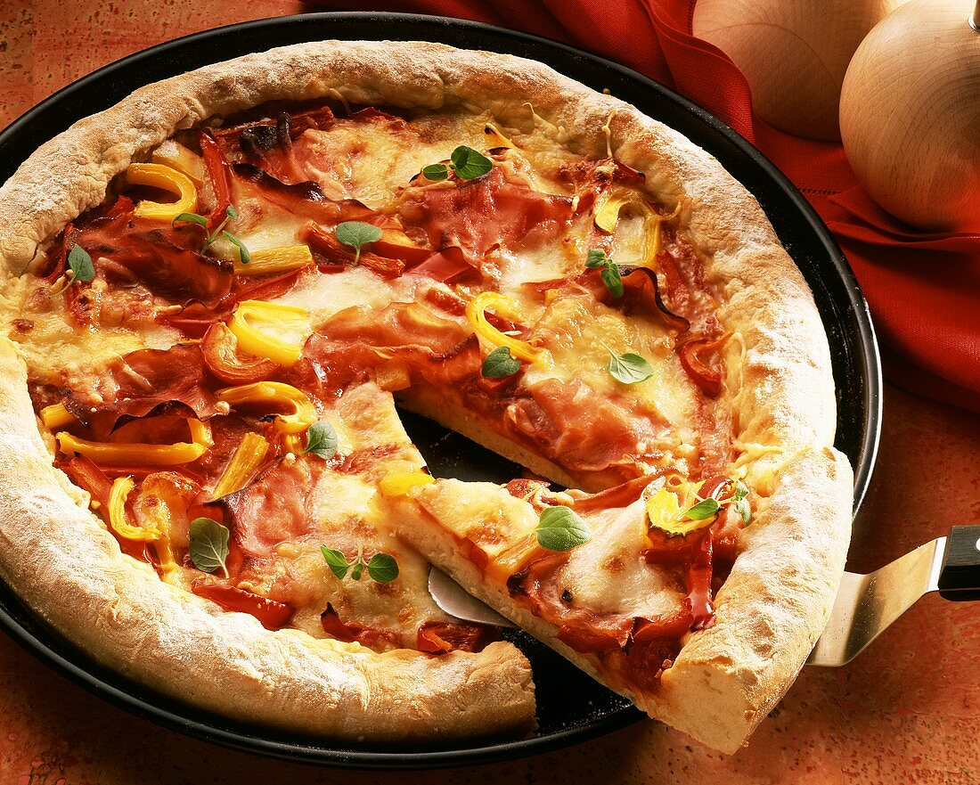 A pizza with ham, tomatoes and pepper
