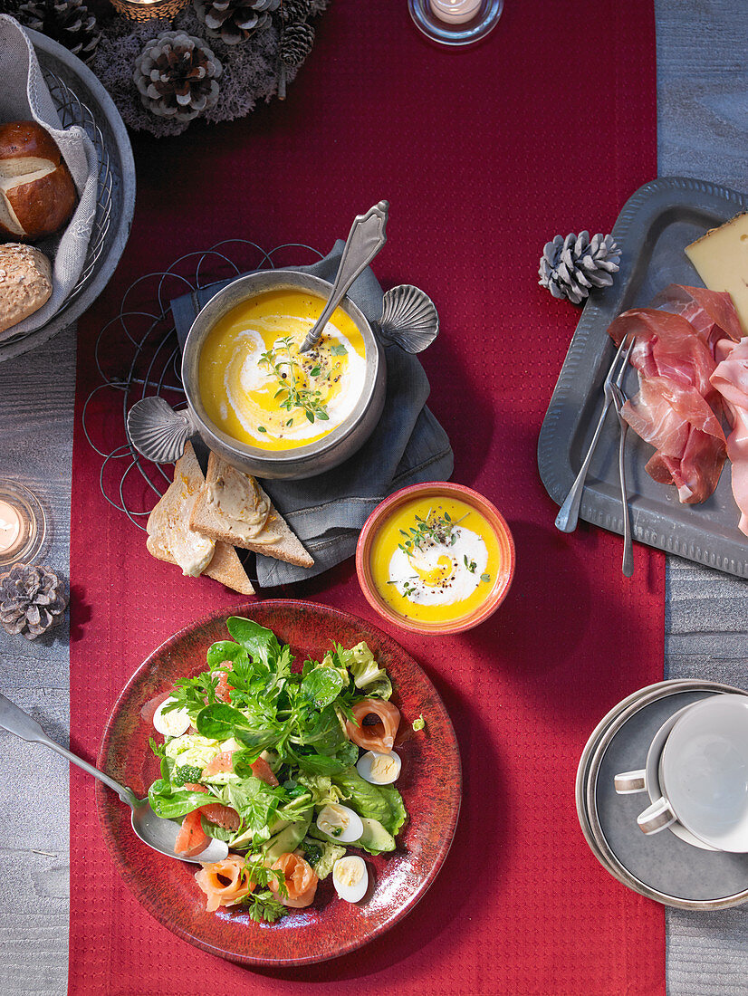 A Christmas buffet with avocado salad and carrot and orange soup