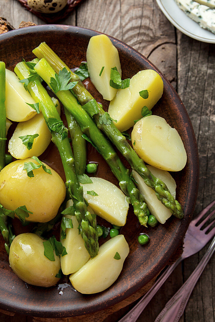 Boiled potato with grilled green asparagus on brown plate over on old wooden background