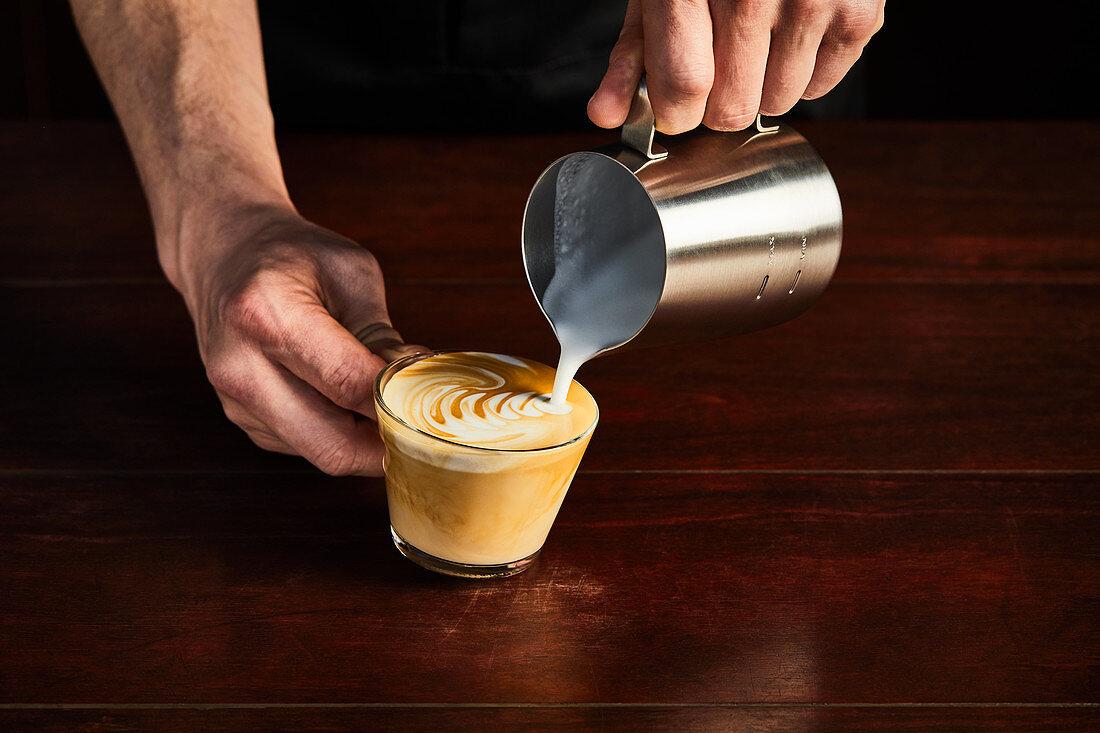 A man preparing a caffe latte