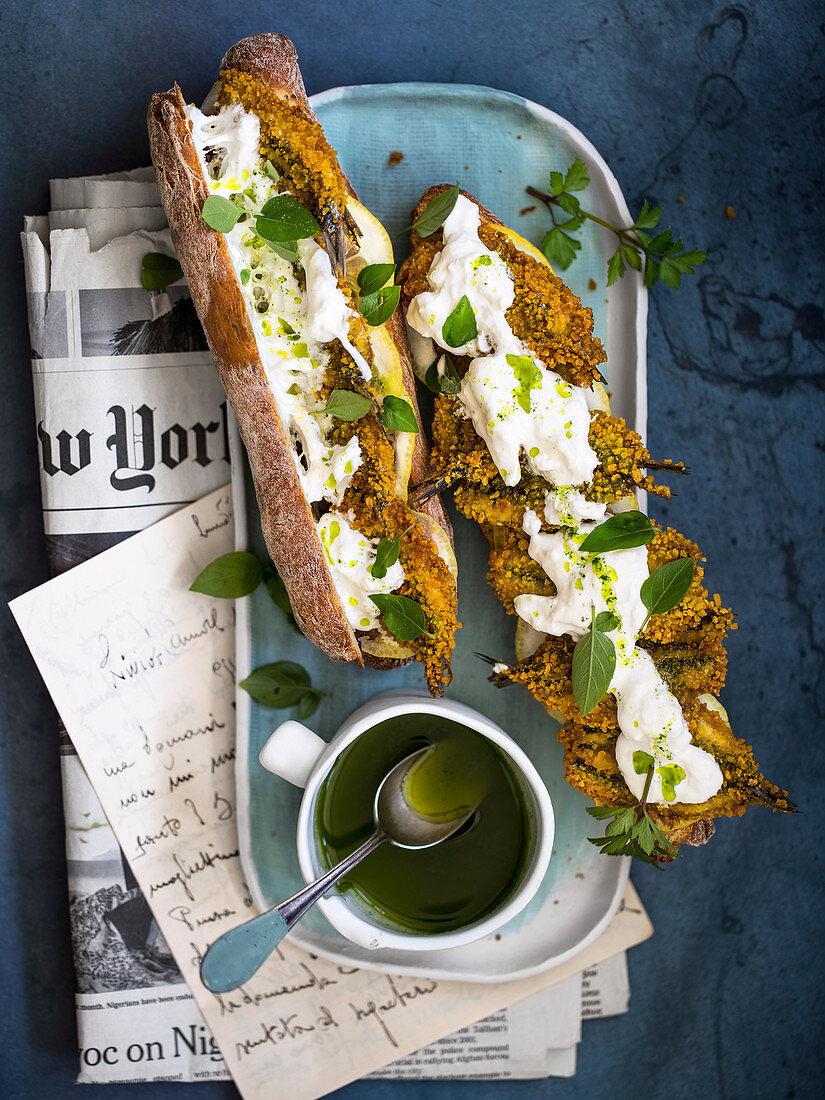 A baguette sandwich with baked sardines, lemon and burrata