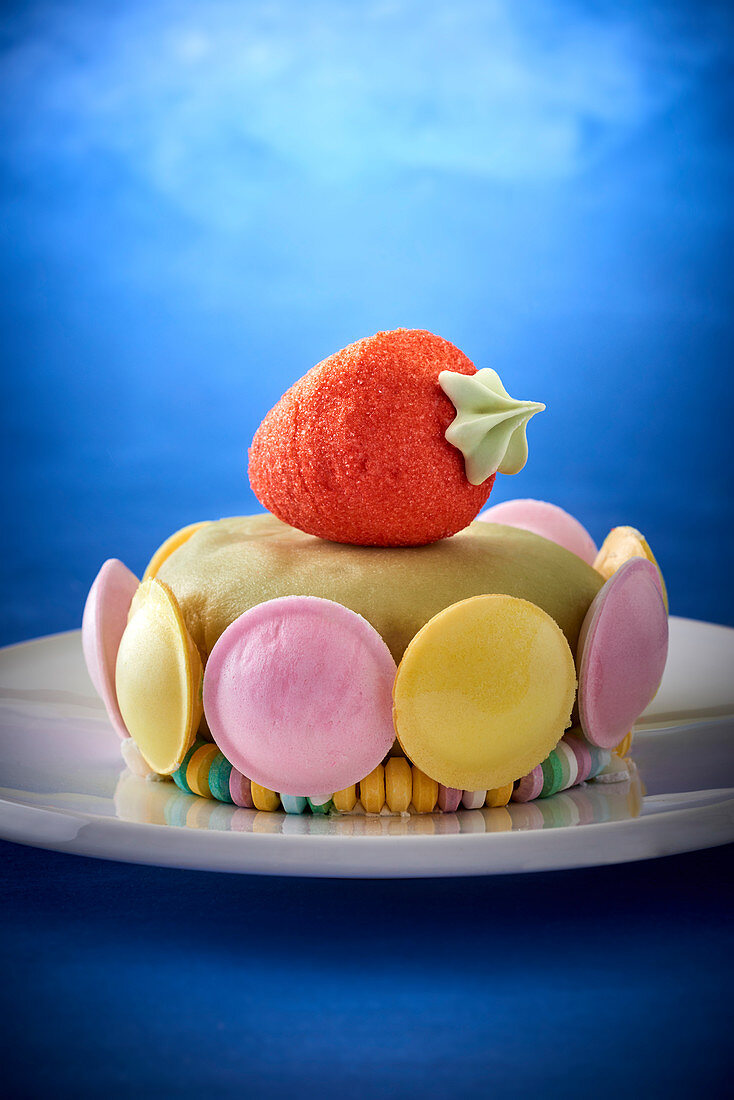 A children's cake with macarons and a strawberry