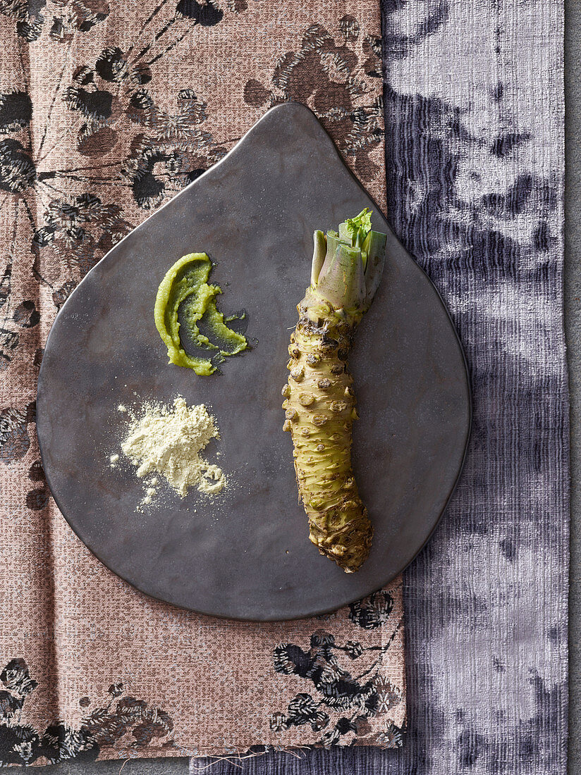 An arrangement of wasabi with wasabi root, powder and paste
