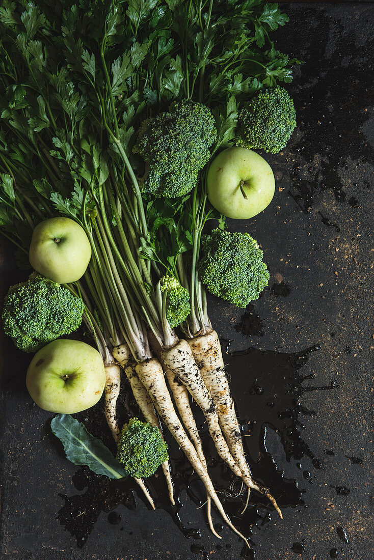 A bunch of parsley, broccoli florets and green apples on dark background