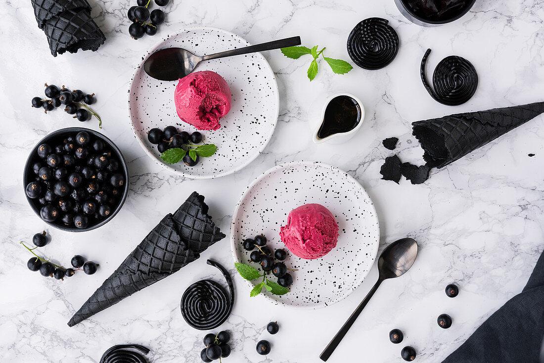 Liquorice ice cream with blackcurrants on white dessert plates