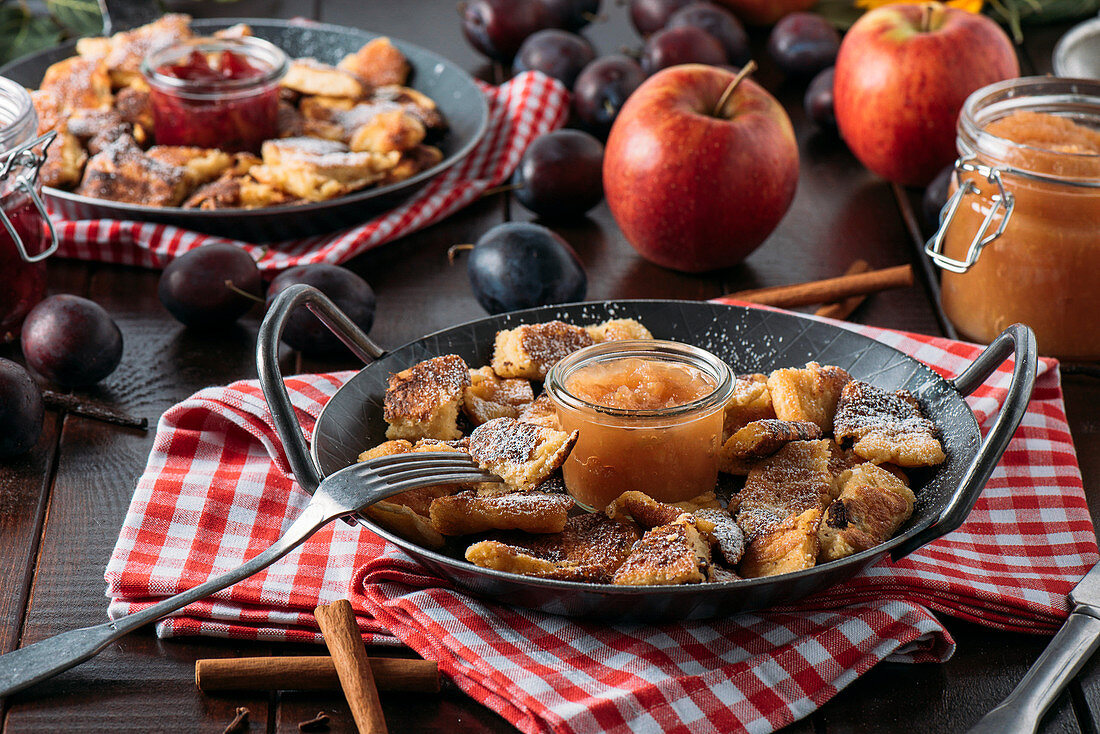 Bohemian Kaiserschmarrn with applesauce and roast plums in a cast-iron pan on a red and white cloth