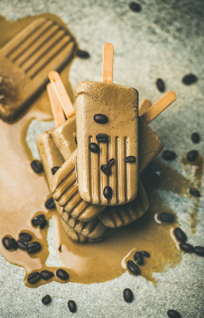 Flatlay of melting coffee latte popsicles with coffee beans