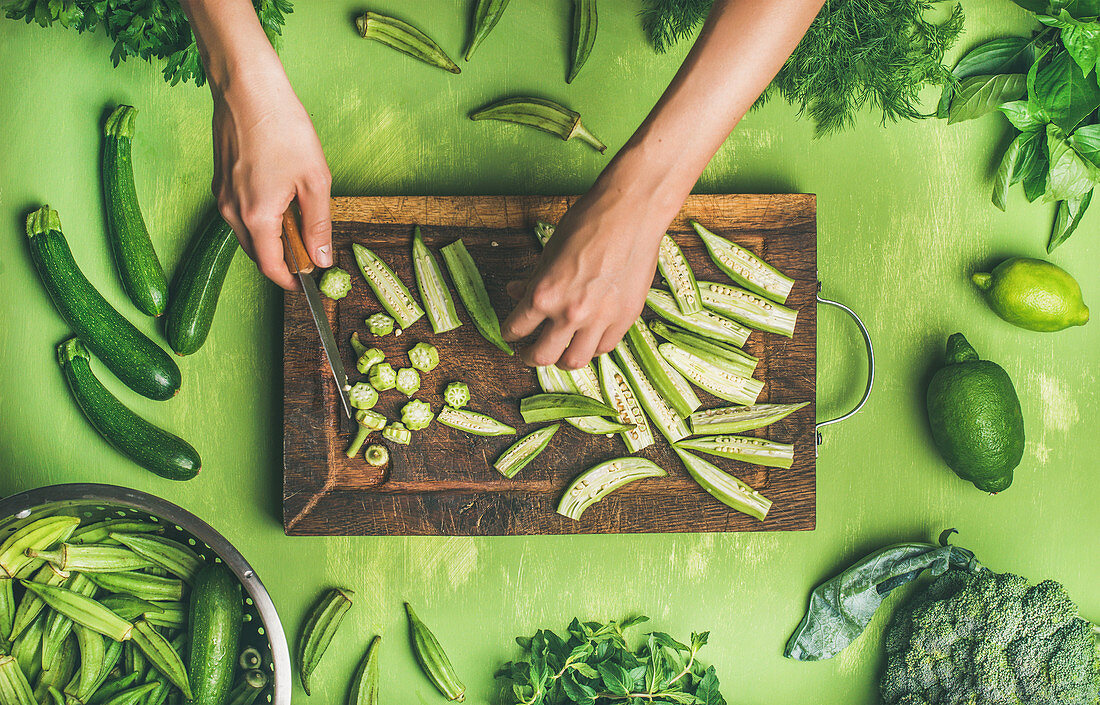 Healthy vegan cooking ingredients - flay-lay of female hands cutting green vegetables and greens on board