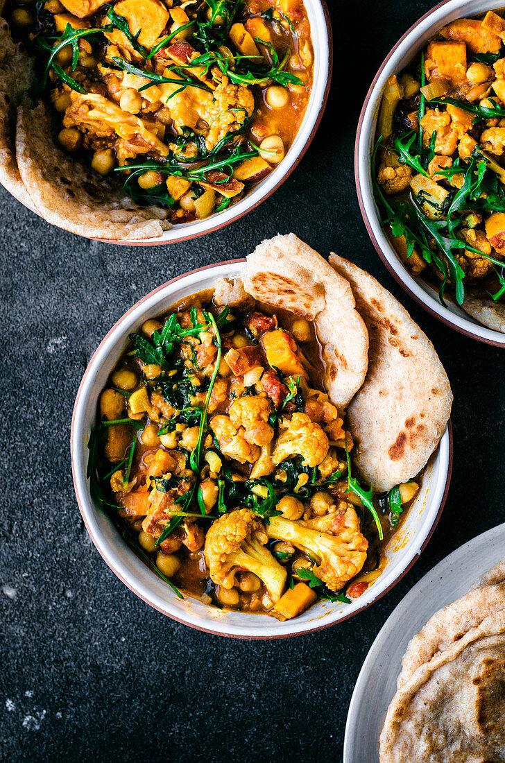 Cauliflower sweet potato curry with arugula and naan