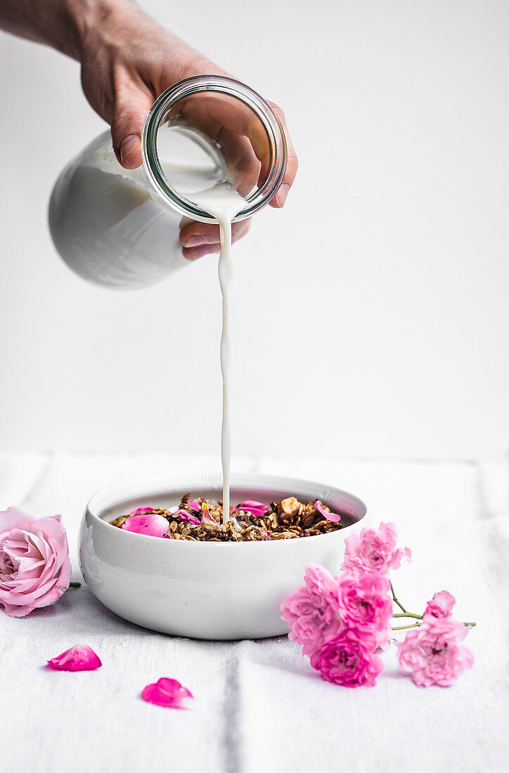 Almond, date, and cardamom granola with rosewater and rose petals, in bowl on linen with milk pouring