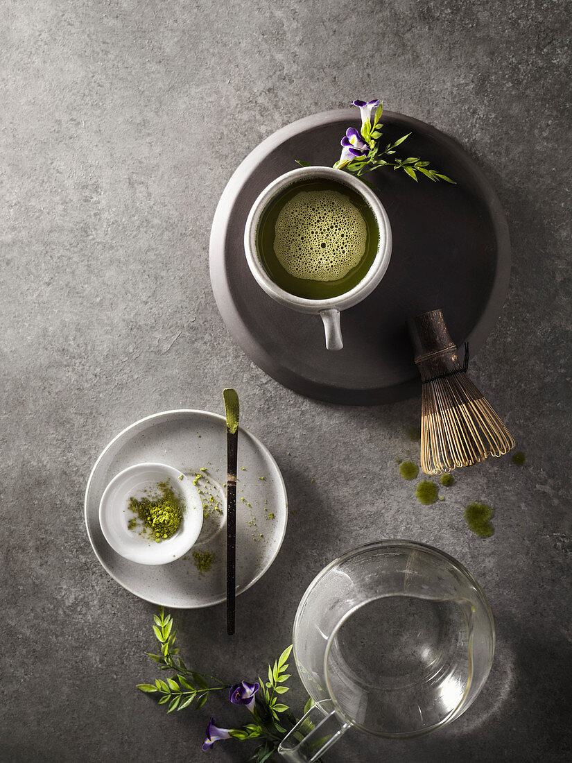 A warm cup of matcha green tea that has just been prepared with wooden whisk and teapot in the background