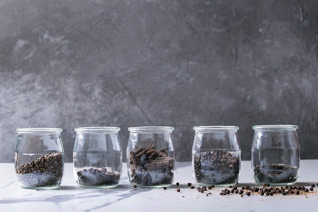 Variety of different black peppers allspice, pimento, long pepper, monks pepper, peppercorns and ground powder in jars