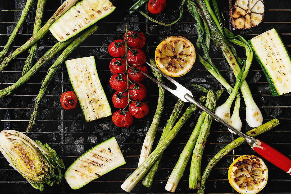 Grilled vegetables green asparagus, garlic, lemon, spring onion, zucchini, cherry tomatoes, salad on bbq grill rack over charcoal