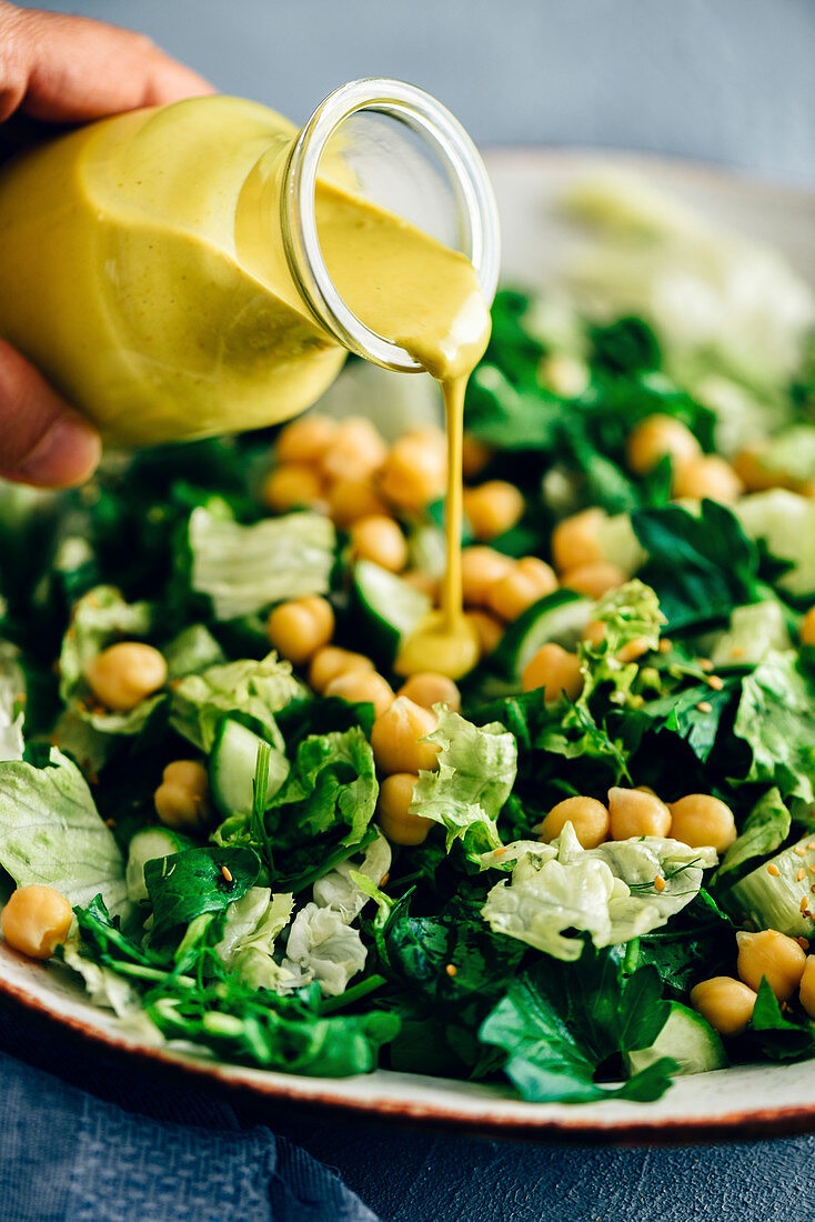 A woman pouring turmeric tahini dressing over a bowl of green salad with chickpeas