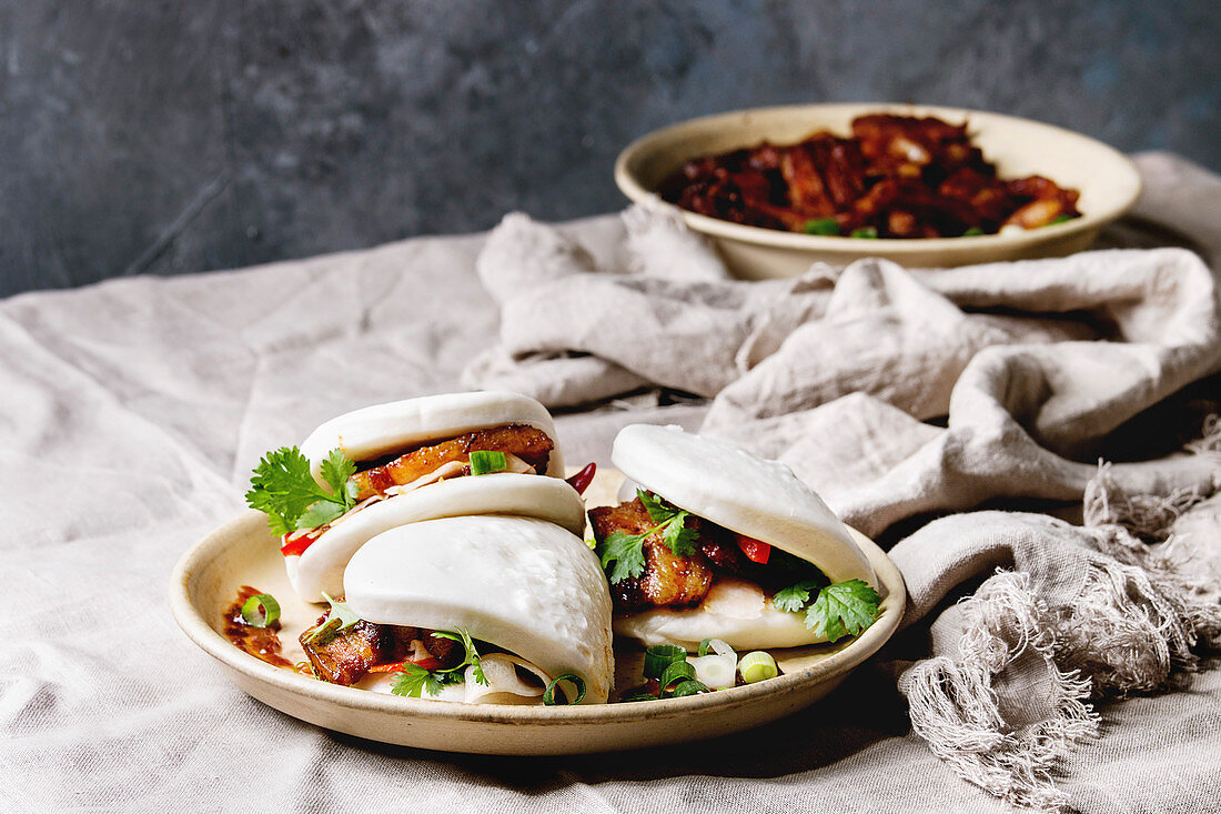 Asian sandwich steamed gua bao buns with pork belly, greens and vegetables served in ceramic plate