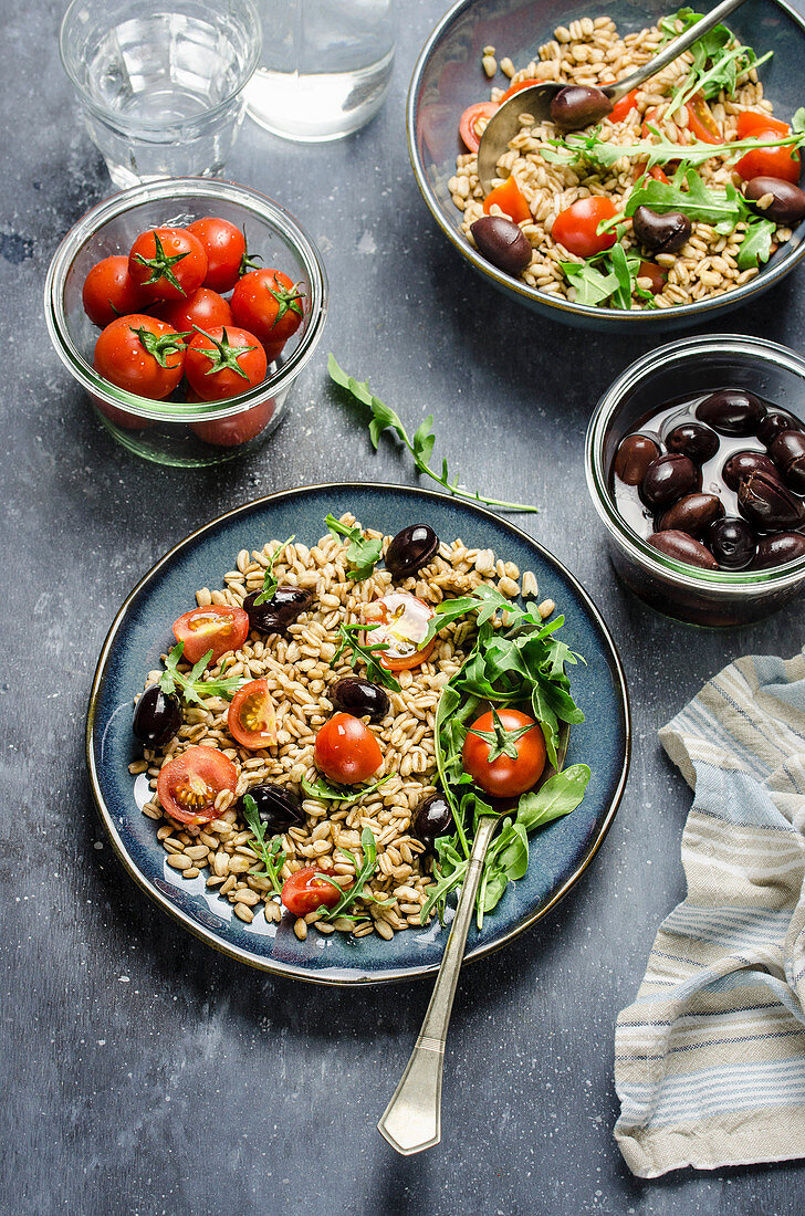 Farro spelt salad with cherry tomatoes, black olives and arugula