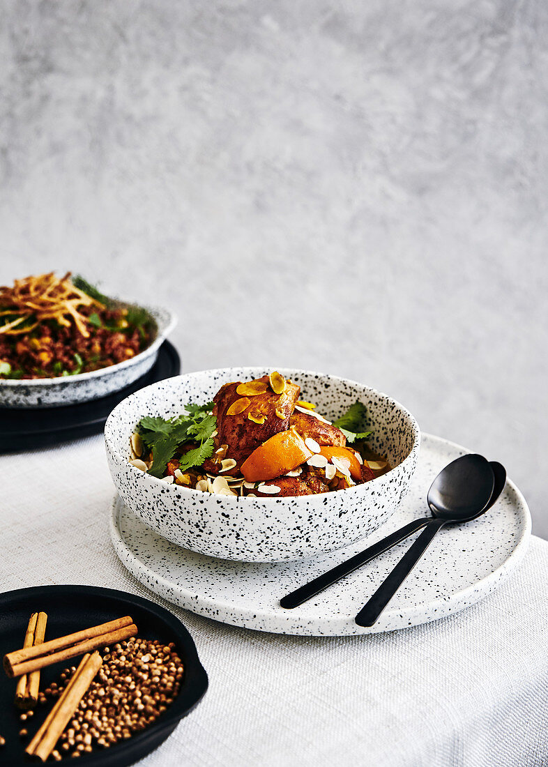 Chicken and persimmon tagine with almonds, coriander. side dish of red rise and chickpeas with fried onions with fresh herbs.